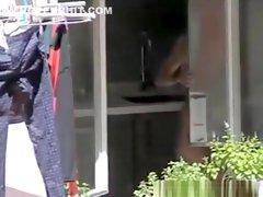 Voyeur films hot chick through her kitchen window