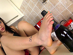 Model shows off her feet while rubbing a wide bottle